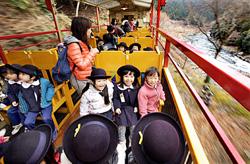 Excited kindergarten pupils smile aboard the tram running along the Hozukyo Gorge (March 1, Nishikyo Ward, Kyoto City, near Hozukyo Torokko Station)