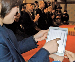 A participant traces the sutra on a tablet screen while following the priests' chanting (Jodo-in, a subsidiary temple of Byodo-in Temple, Uji City, Kyoto Prefecture)