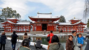 Photo= Families take pictures of the recently repaired, snow-covered Phoenix Hall (Byodo-in Temple, Uji City, Kyoto Prefecture)