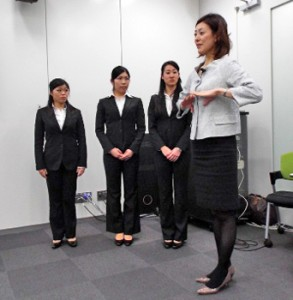 Photo= University women who are learning the beautiful way to walk from Tani, at right = Omron Healthcare Tokyo Office, Minato Ward, Tokyo