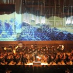 Photo= The Kyoto Symphony Orchestra plays against a background of images projected on the wall (Kyoto Concert Hall, Sakyo Ward, Kyoto)