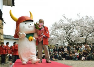 Photo= Hikonyan expressing his happiness in front of gathered fans as he receives flowers to celebrate his birthday (Before Hikone Castle tower, Konki-cho, Hikone City, Shiga Prefecture)