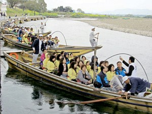 Photo= A group of travelers from Taiwan set off downstream in a long string of boats (Hozu-cho, Kameoka City, Kyoto Prefecture)