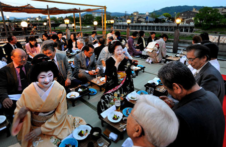 Photo= People enjoying a meal with Geiko and Maiko on the terrace as the river breeze blows (May 1, Nakagyo Ward, Kyoto)