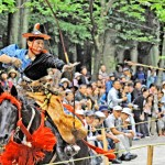 Photo= As many spectators watch, an archer on a galloping horse shoots an arrow (June 7, Oumi-Jingu Shrine, Jingu-cho, Otsu City, Shiga Prefecture)
