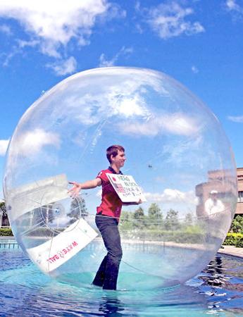"Photo= A man dancing in a water ball while holding the panel that says ""Go around Lake Biwa by bike"" (Biwako Hotel, Hamamachi, Otsu City, Shiga Prefecture)"