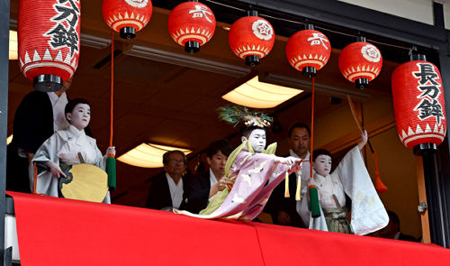 """Photo= Naito (center), this year's Chigo, leans forward and performs the """"Taihei-no-mai"""" dance with Kamuro assistants, Yamashiro (left) and Hara (July 5, Naginata Hoko Town Hall, Shijo-dori Karasumahigashi-iru, Shimogyo Ward, Kyoto)"""