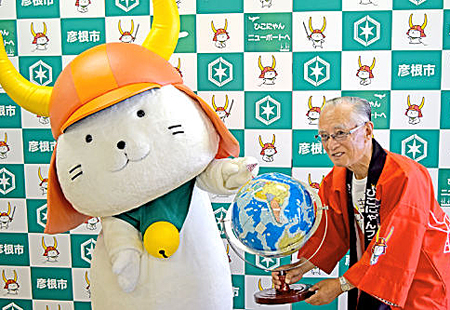 "Photo= ""Hikonyan"" joyfully pointing to Newport's location on the globe with his traveling companion, the fan club president, Kitamura (city hall, Hikone City, Shiga Prefecture)"