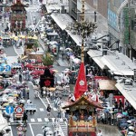 Photo= The float procession proceeds along Shijo-dori Street in the rain. The Kanko Boko float is in front (July 17, looking west from Shijo-dori Teramachi, Shimogyo Ward, Kyoto)