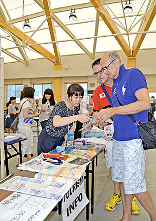 Photo= A foreign passenger making inquiries of a staff member at the terminal building's tourist information center (2nd Wharf, Maizuru West Port, Matsukage, Maizuru City, Kyoto Prefecture)