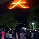 "Photo= Many citizens watch the ""Daimonji"" bonfire to send off the spirits of ancestors (August 16, eastward view from near Demachi-bashi on the Kamo River, Kamigyo Ward, Kyoto)"