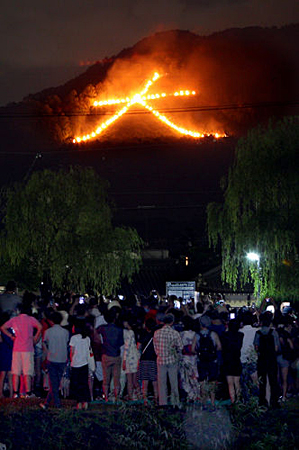 """Photo= Many citizens watch the """"Daimonji"""" bonfire to send off the spirits of ancestors (August 16, eastward view from near Demachi-bashi on the Kamo River, Kamigyo Ward, Kyoto)"""