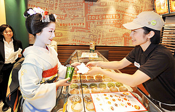 """Photo= A Maiko, carrying her own water bottle to receive """"Kyoto Eco Money,"""" smiles at the store clerk (September 29, Kyoto City Subway Line's Shijo Station, Shimogyo Ward, Kyoto)"""