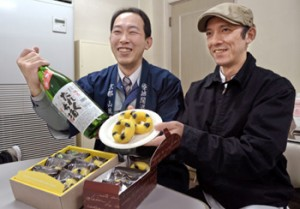 """Photo= Mr. Sato, Sucre's owner (right) and Mr. Shimamoto, president of Joyo-Shuzo, smile as they hold up the baked sweet, """"Tarekuchi,"""" which contains """"Namagenshu Tarekuchi-zake""""= Joyo-Shuzo, Nashima, Joyo City, Kyoto Prefecture"""