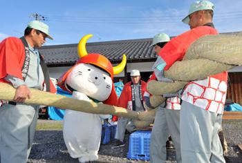 Photo= Hikonyan helps to twist huge straw ropes for New Year's decorations (Within Hikone Castle, Konki-cho, Hikone City, Shiga Prefecture)