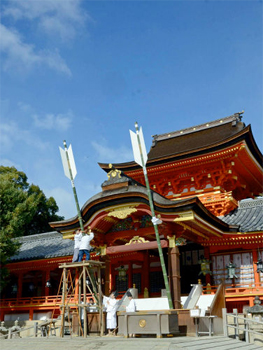 Photo= Under clear blue skies, Shinto priests set up Jumbo Goshinya in front of the main shrine (Iwashimizu Hachimangu Shrine, Yawata, Yawata City, Kyoto Prefecture)