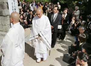 "Photo= Kogen Kamahori (center) enters the temple for the ""Sennichi-Kaiho-Gyo"" pilgrimage, watched over by worshipers and his relatives (Myo-o-do Temple, Mudojidani, Sakamoto Honmachi, Otsu City, Shiga Prefecture)"
