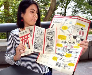Photo= Ikegawa holds the guide maps she designed for foreign tourists visiting Fushimi Inari Taisha Shrine (Kyoto University of Art and Design, Sakyo Ward, Kyoto)