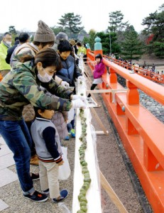 Photo= Participants closely arrange tea-flavored sweet dumplings one by one with no gaps between them (Asagiribashi Bridge, Uji, Uji City, Kyoto)