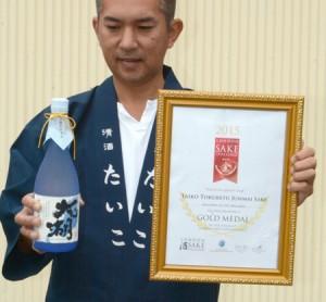 "Photo= President Sato holding ""Taiko"" which was awarded the gold prize at the London Sake Challenge, along with the award certificate (Sato Syuzo. Co., Ltd, Enoki-cho, Nagahama City, Shiga Prefecture)"