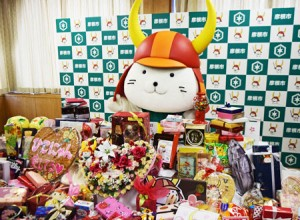 Photo= Hikonyan showing his joy in front of the mountain of Valentine's Day gifts he received (Hikone City Hall, Hikone City, Shiga Prefecture)