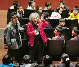 "Photo= Conductor Seiji Ozawa (center) talks about the stage to the invited elementary school students before performing the operetta ""Die Fledermaus"""