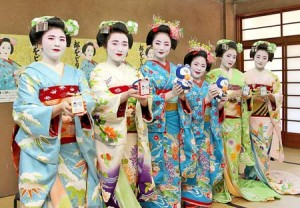 Photo= Maiko holding audio guide devices with earphones (Higashiyama Ward, Kyoto)