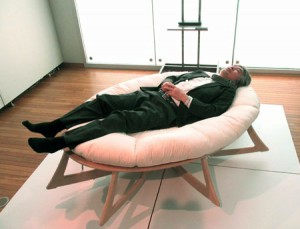 """Photo= Juichi Yamagiwa, President of Kyoto University, lies on the """"Human Evolution Bed."""" He rated it highly, saying, """"I feel perfectly relaxed, with my head and feet raised up."""" (Kyoto University Museum, Sakyo Ward, Kyoto)"""