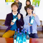 "Photo= Students from the Japanese sake project at the University of Shiga Prefecture show their finished product, the new sake ""Kofuu,"" and newly produced posters (Hikone City Hall, Shiga Prefecture)"