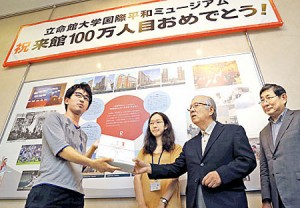 Photo= Higa (left), who became the one-millionth visitor and received a commemorative gift = 11:10 a.m., August 3, Kyoto Museum for World Peace, Ritsumeikan University, Kita Ward, Kyoto