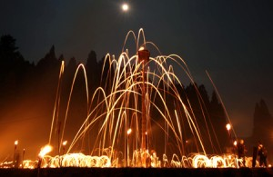 "Photo = The ""Hanase Matsuage"" ritual, with the released flames drawing arcs to the Torogi log and illuminating the night sky (9:06 p.m., August 15, Hanase, Sakyo Ward, Kyoto)"