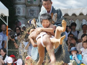 Photo= Elementary school students wrestling with all their strength kick up clouds of dust from the ring (September 9, Kamigamo Shrine, Kita Ward, Kyoto)