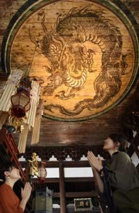 Photo= Visitors clap their hands and listen attentively to the sound, as they look up at the Banryu-zu (Shokoku-ji Temple, Kamigyo Ward, Kyoto)