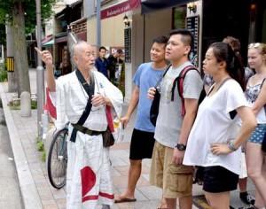Photo= Joe Okada (far left) speaking humorously as he guides foreign tourists around the city in English= Nakagyo Ward, Kyoto