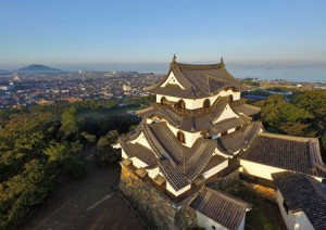 Photo= The main keep with its complicated roof structure shows its dignified appearance. The city and Lake Biwa spread out behind it (Hikone Castle, Hikone City, Shiga Prefecture)= taken by drone