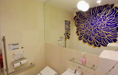 Photo= Ki-Yan's recommended mural of a dahlia in the barrier-free restroom. It is designed so that a large flower expands behind you when you stand in front of the mirror.