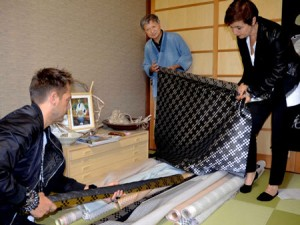 Photo= While listening to an explanation from Koishibara (second from the right), creators of a Paris-based, clothing brand examine silk cloth woven with silver thread and Fujifu = October 24, Yushisha, Amino-cho, Kyotango City, Kyoto Prefecture
