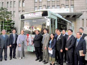 Photo= A deputy director from Vientiane, fourth from left, receives the replica key in front of donated city buses, and others= Kyoto City Hall Plaza, Nakagyo Ward, Kyoto