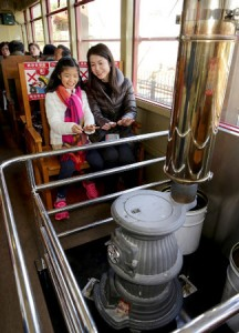 Photo= Passengers warm up on a stove-installed train, which has just begun operation (December 8, Saga Torokko Station, Ukyo Ward, Kyoto)