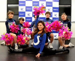 Photo= Shibano, visiting her alma mater, Kyoto Sangyo University, and posing surrounded by the university's cheerleaders (Kita Ward, Kyoto)