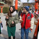 Photo= Tourists receiving pamphlets from women dressed up as characters from an anime set in Fushimi Inari Taisha Shrine (in front of Fushimi Inari Taisha Shrine, Fushimi Ward, Kyoto)
