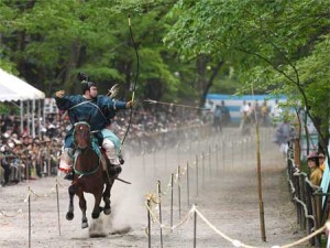 "Photo= An archer shooting an arrow from the back of a galloping horse that is kicking up a cloud of dust, in ""Yabusame Shinji"" (May 3, Shimogamo Shrine, Sakyo Ward, Kyoto)"