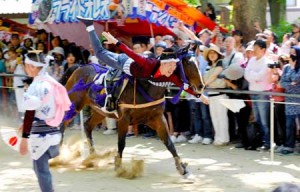 Photo= A trick rider performing a stunt on horseback while numerous spectators watch (May 5, Fujinomori Jinjya Shrine, Fushimi Ward, Kyoto)
