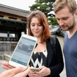 Photo= Foreign tourists viewing the audio-guidance smartphone app in front of the Kyoto Imperial Palace's Kenrei-mon Gate (May 16, Kyoto Gyoen National Garden, Kamigyo Ward, Kyoto)