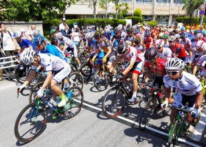 Photo= Cyclists off and running at the start of Kyoto Stage, Tour of Japan (May 22, in front of Fugenji Elementary School, Kyotanabe City, Kyoto Prefecture)