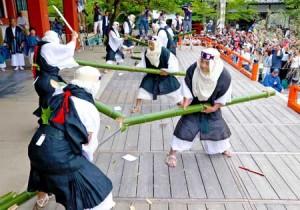 Photo= Men dressed as warrior monks dynamically slashing green bamboo representing great serpents (June 20, Kurama-dera Temple, Sakyo Ward, Kyoto)