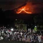 "Photo= A crowd of people watch as the character ""Daimonji"" emerges to illuminate the darkness (August 16, eastward view from Demachi-bashi Nishizume, Kamigyo Ward, Kyoto)"