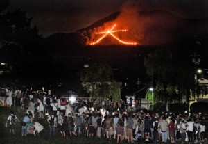 """Photo= A crowd of people watch as the character """"Daimonji"""" emerges to illuminate the darkness (August 16, eastward view from Demachi-bashi Nishizume, Kamigyo Ward, Kyoto)"""