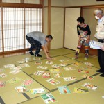 Photo= Participants learning how to prepare for a disaster and how to act when one occurs, while enjoying a disaster prevention card game (Hito Machi Koryukan Kyoto, Shimogyo Ward, Kyoto)