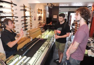 Photo= Foreign visitors receive explanations about practice swords used for Iaido from staff at a martial arts equipment store (Tozando Shogoin Store, Sakyo Ward, Kyoto)